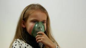 Sidosikt av den härliga caucasian tonåriga bärande maskeringen och att andas för inhalator lager videofilmer