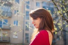 Sidosikt av den härliga gladlynta flickan med gulliga sinnliga kanter som tycker om våren i staden under solig dag livsstil arkivbilder