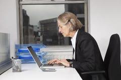 Sidosikt av den höga affärskvinnan som i regeringsställning använder bärbara datorn på skrivbordet Arkivfoto