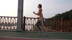 Sidosikt av den höga kvinnan som joggar över bron stock video