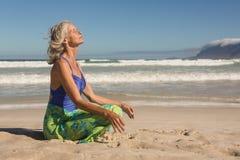 Sidosikt av den höga kvinnan som mediterar, medan sitta på kust arkivfoton