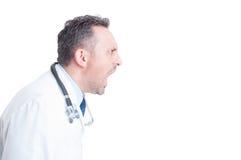 Sidosikt av den ilskna läkaren eller doktorn som skriker och ropar Arkivfoton