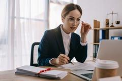 sidosikt av den kvinnliga advokaten som gör skrivbordsarbete på arbetsplatsen med bärbara datorn arkivfoton