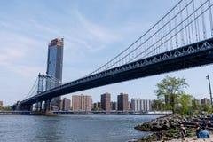 Sidosikt av den Manhattan brostrukturen och New York byggnader arkivbilder