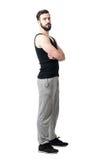 Sidosikt av den muskulösa idrottsman nen i ärmlös tröja med korsade armar som ser kameran royaltyfri fotografi