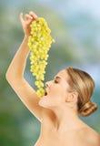 Sidosikt av den näcka kvinnan som äter druvor Arkivfoton