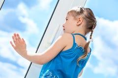 Sidosikt av den nätta flickan bak plast- fönsterexponeringsglas Arkivfoton