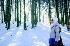 Sidosikt av den nätta unga kvinnan utomhus på blå himmel och frostig trädbakgrund Royaltyfri Bild