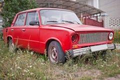 Sidosikt av den röda gamla rostiga bilen Royaltyfri Fotografi
