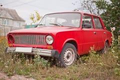 Sidosikt av den röda gamla rostiga bilen Royaltyfri Bild
