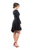 Sidosikt av den sofistikerade kvinnan för flott glamour i den svarta klänningen som bort ser arkivfoton