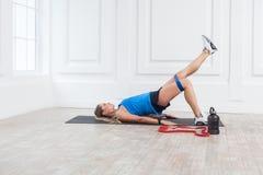 Sidosikt av den stark och för passform idrotts- unga caucasian kvinnan i sportwear med musikband som utbildar ben, och muskulösa  royaltyfria foton