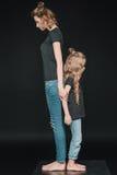 Sidosikt av den stilfulla den stående dottern och modern tillbaka att dra tillbaka Royaltyfria Bilder