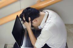 Sidosikt av den stressade upprivna unga asiatiska affärsmannen med händer på pannan i fördjupning arkivfoton