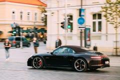 Sidosikt av den svarta Porsche 991 Targa 4S bilen som är rörande på gatan bil Royaltyfria Bilder