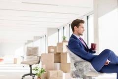 Sidosikt av den unga affärsmannen som har kaffe på stol i nytt kontor arkivfoton