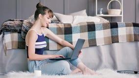 Sidosikt av den unga attraktiva kvinnliga tonåringen som använder bärbar datorsammanträde på fluffig vit matta stock video