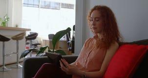 Sidosikt av den unga caucasian affärskvinnan som arbetar på den digitala minnestavlan i ett modernt kontor 4k arkivfilmer