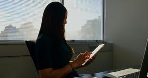 Sidosikt av den unga caucasian aff?rskvinnan som arbetar p? den digitala minnestavlan i ett modernt kontor 4k arkivfilmer