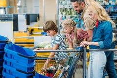 sidosikt av den unga familjen med shoppingvagnen mycket av köp royaltyfri foto