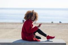 Sidosikt av den unga h?rliga lockiga afrikansk amerikankvinnan som sitter p? en b?nk p? stranden, medan genom att anv?nda en mobi royaltyfri foto