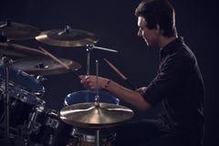 Sidosikt av den unga handelsresanden Playing Drum Kit In Studio royaltyfria foton