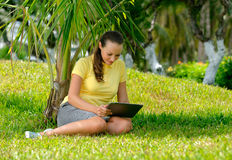 Sidosikt av den unga kvinnan på gräsmattan med hennes minnestavladator Royaltyfri Bild
