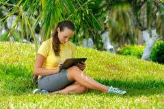 Sidosikt av den unga kvinnan på gräsmattan med hennes minnestavladator Royaltyfri Fotografi