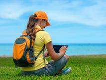 Sidosikt av den unga kvinnan på gräsmattan med hennes minnestavladator Arkivfoton