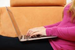 Sidosikt av den unga kvinnan som använder bärbara datorn på soffan Arkivbild
