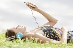 Sidosikt av den unga kvinnan som lyssnar till musik till och med spelaren MP3, medan ligga på gräs mot himmel Arkivbild
