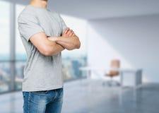 Sidosikt av den unga mannen i en grå t-skjorta med korsade händer Arkivbild