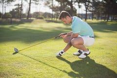 Sidosikt av den unga mannen som förlägger golfboll på utslagsplats arkivbild