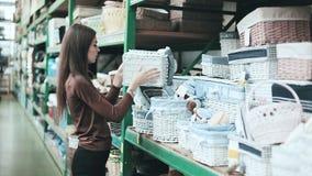 Sidosikt av den unga nätta kvinnan med den långa köpandekorgen för mörkt hår på supermarket Flicka som väljer objekt på hushållla stock video