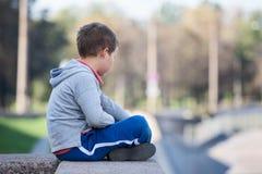 Sidosikt av den unga positionen för pojkesammanträdelotusblomma på granittrottoarkant Royaltyfri Foto
