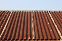Sidosikt av det mycket tenn- taket som är gammalt med rostig och liten blå himmel upptill Royaltyfri Bild