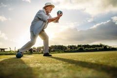 Sidosikt av en äldre man som spelar boules royaltyfria bilder