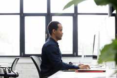 Sidosikt av en afrikansk affärsman som arbetar på en dator arkivfoto