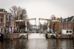 Sidosikt av en berömd träklaffbro som ses från vattnet med byggnader i bakgrunden i Amsterdam royaltyfri foto