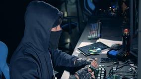 Sidosikt av en förklädd en hacker som arbetar på datoren arkivfilmer