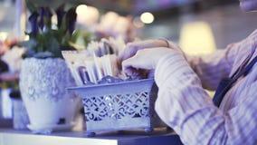 Sidosikt av en försäljare som väljer en vykort för en blommagrupp, pannaskott lager videofilmer