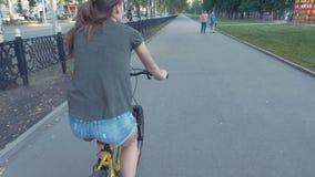 Sidosikt av en flicka som cyklar på en väg med blommor i en korg och undersöker staden, långsam mo, steadicamskott arkivfilmer