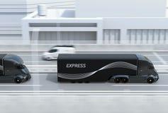 Sidosikt av en flotta av svarta själv-körande elektriska halva lastbilar som kör på huvudvägen arkivfoto