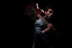 Sidosikt av en gitarrist som rymmer hans gitarr på skuldra arkivbilder