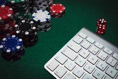 Sidosikt av en grön pokertabell med några pokerkort på ett tangentbord Slå vad on-line begrepp arkivfoton