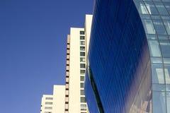 Sidosikt av en krökt blå vägg för glass fönster av ett modernt och elegant corporative höghus, bredvid ett gulaktigt klassiskt royaltyfri bild