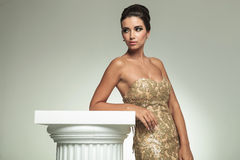 Sidosikt av en kvinna i klänningbenägenhet på kolonn Royaltyfri Foto