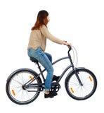 Sidosikt av en kvinna med en cykel Royaltyfri Foto