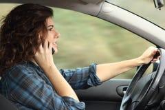 Sidosikt av en kvinna som kör en bil och talar på telefonen Royaltyfri Foto