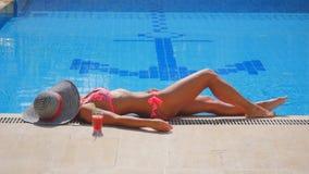Sidosikt av en kvinna som kopplar av nära simbassängen arkivfilmer